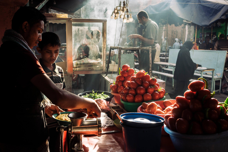 أكشاك الطعام في سوق الملح، في مدينة صنعاء القديمة، العاصمة. هنا، كما في أي مكان آخر في شمال اليمن، لا يوجد نقص في الغذاء. لكن الأسعار مرتفعة لدرجة أن معظم الناس لم يعودوا قادرين على تلبية احتياجاتهم الأساسية.